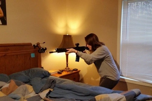 Woman Holding Rifle In Bedroom