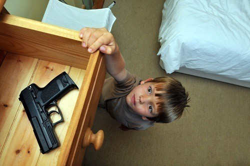 Little Boy Reaching For A Gun In Tray