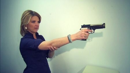 Woman holding smart gun.