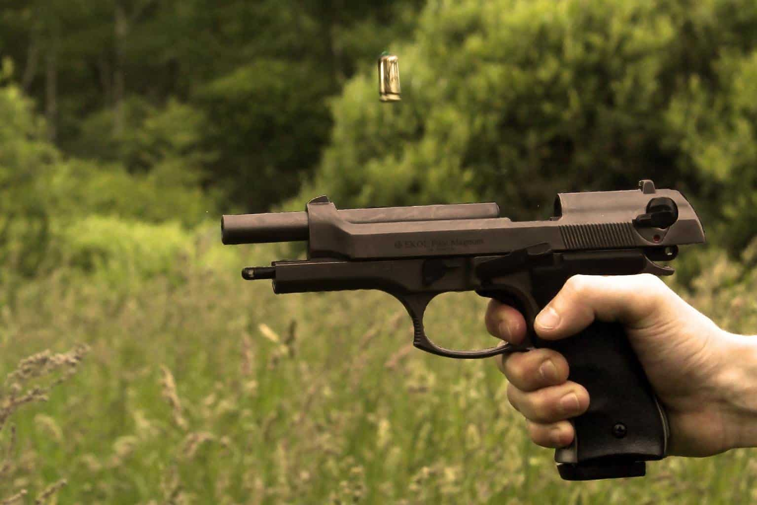 Semi automatic pistol held at shooting point within a grassy land