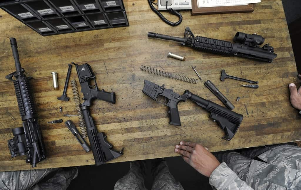 A group of black firearms are laid on top of a wooden table
