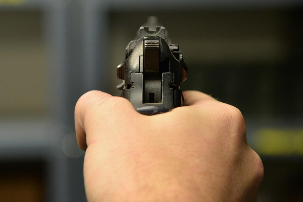 Close up of a man's hand holding a handgun