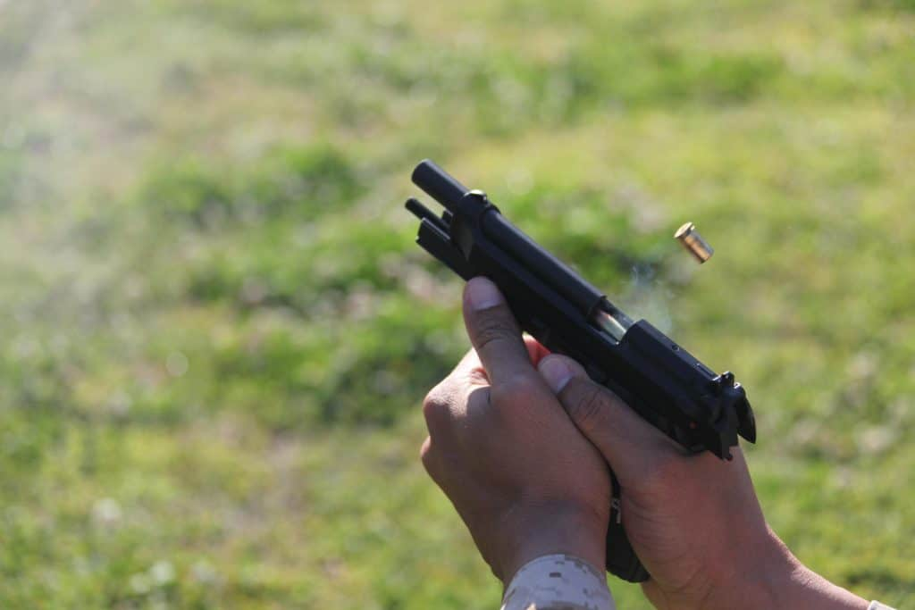 A man's hand holding a handgun while reloading it