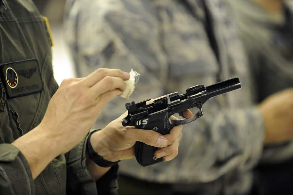 Man holding a handgun wiping it with a cotton pad