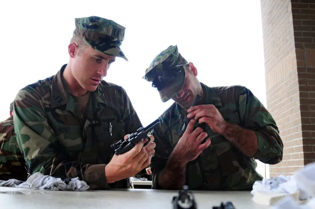 two soldeiers checking the guns for excess debris