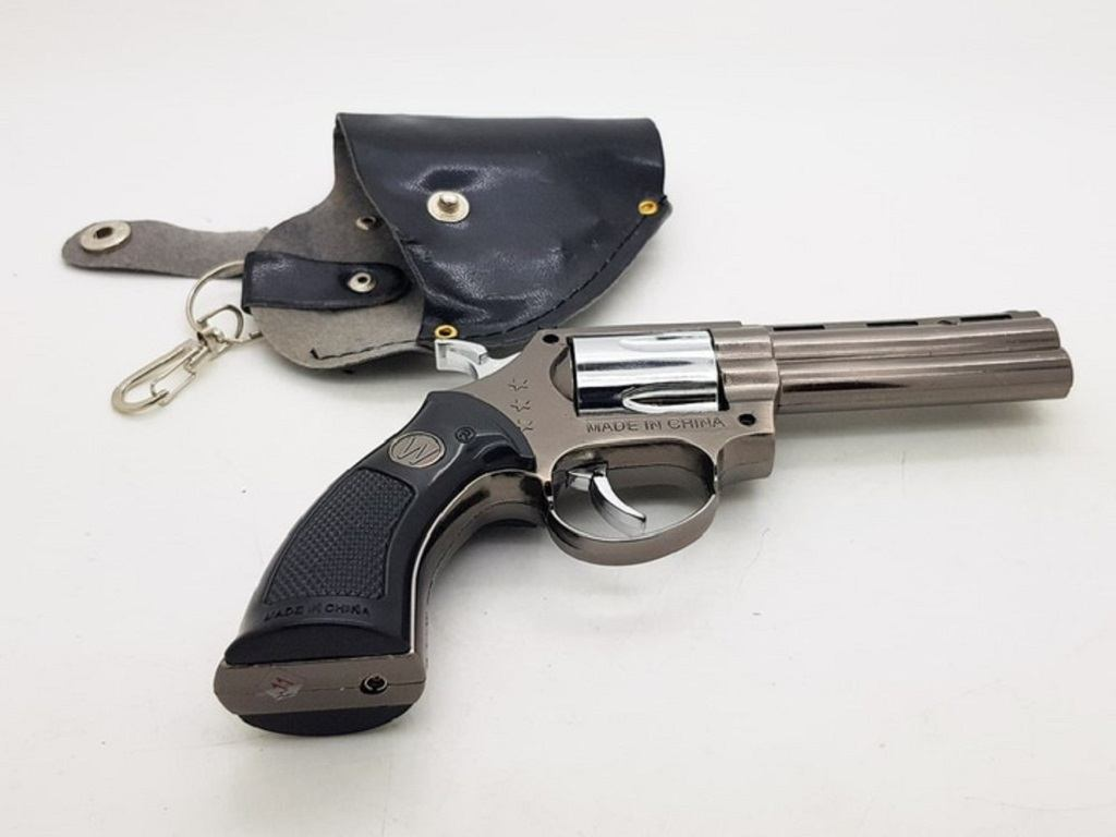 A revolver and a revolver holder on a white table