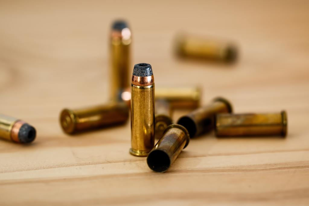 Gold ammunition standing up beside other that are laid on the counter