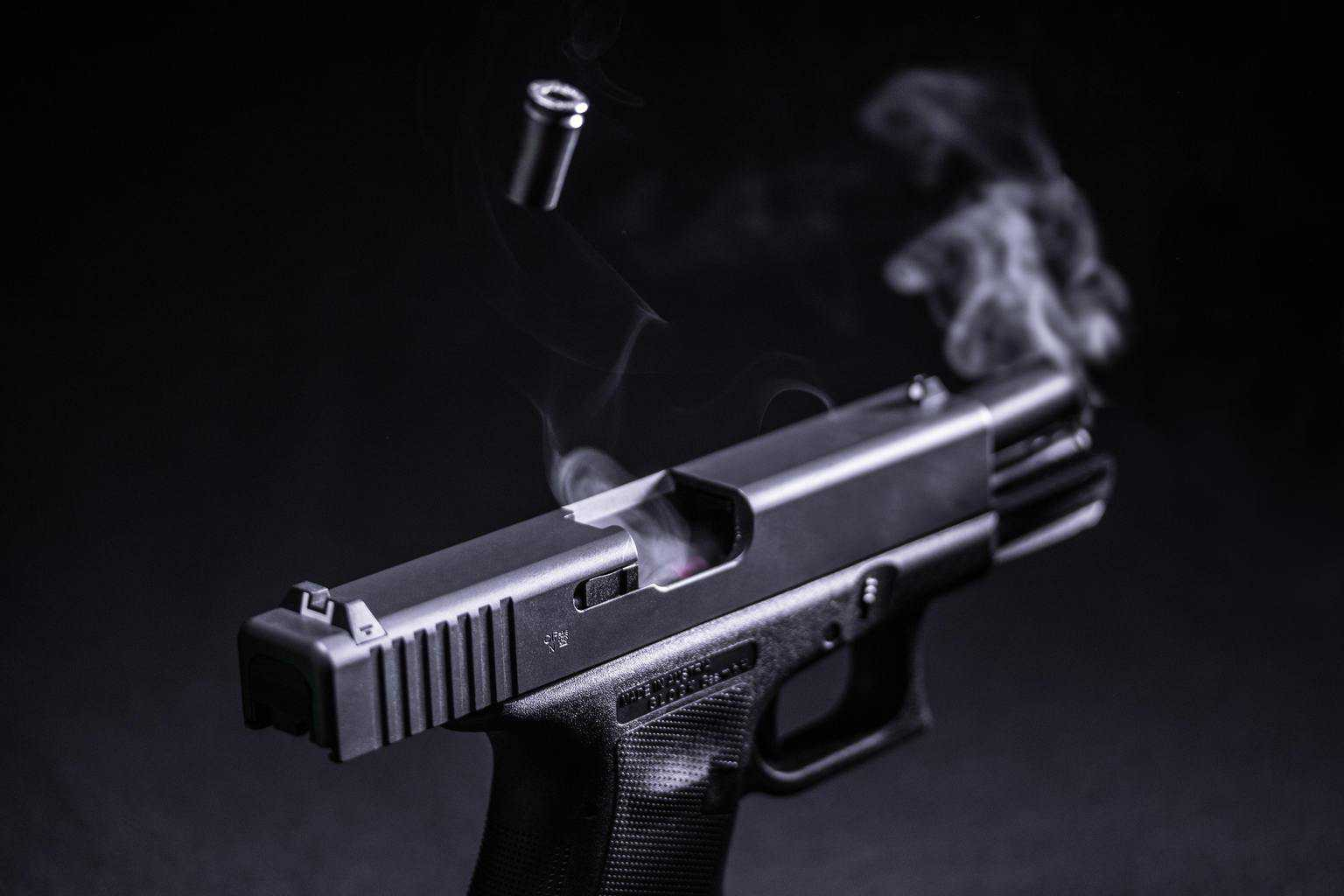 A black hand gun in front of a black background with smoke and bullets coming out of it