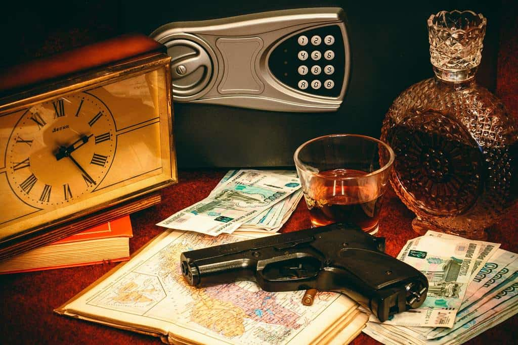 Hand gun beside a bottle and a glass of whisky, a vault and a clock