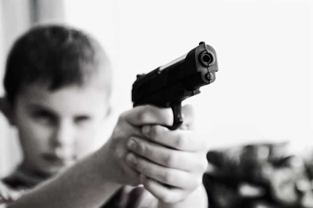 Kid holding up a gun with his finger on the trigger