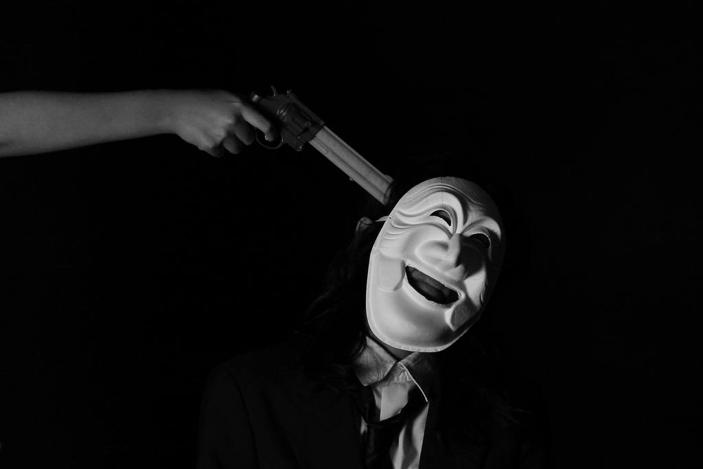 Anonymous hand pointing a gun at the man with a white smiling mask