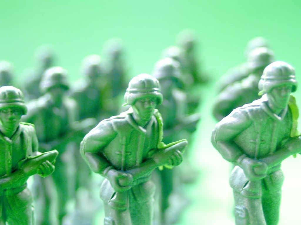 A group of green toy soldiers holding a gun