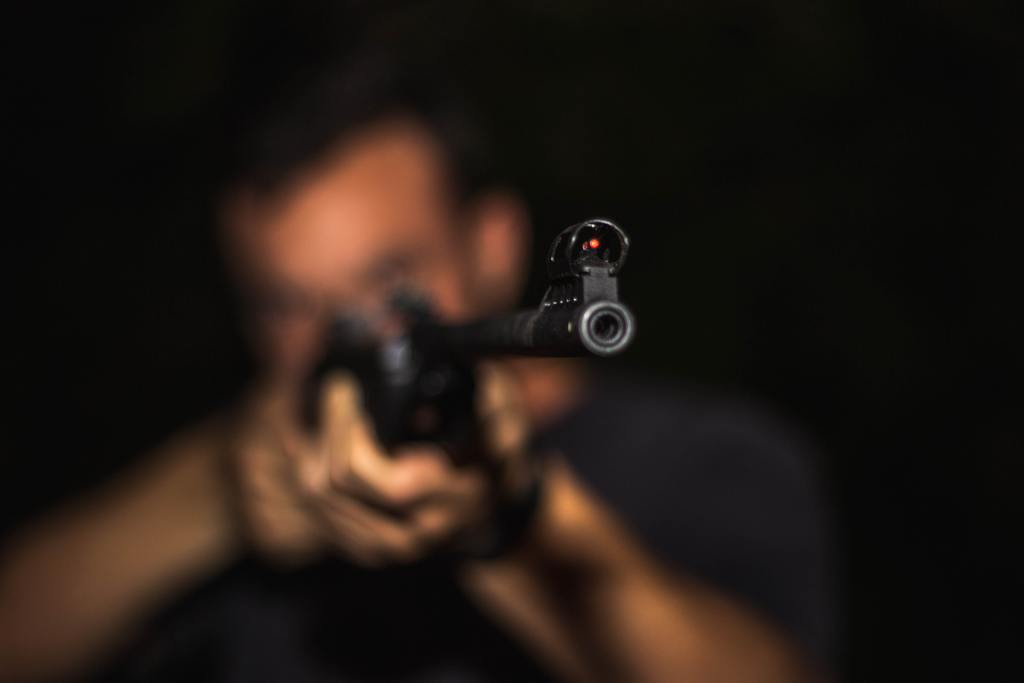 A soft focused photo of a man holding a rifle
