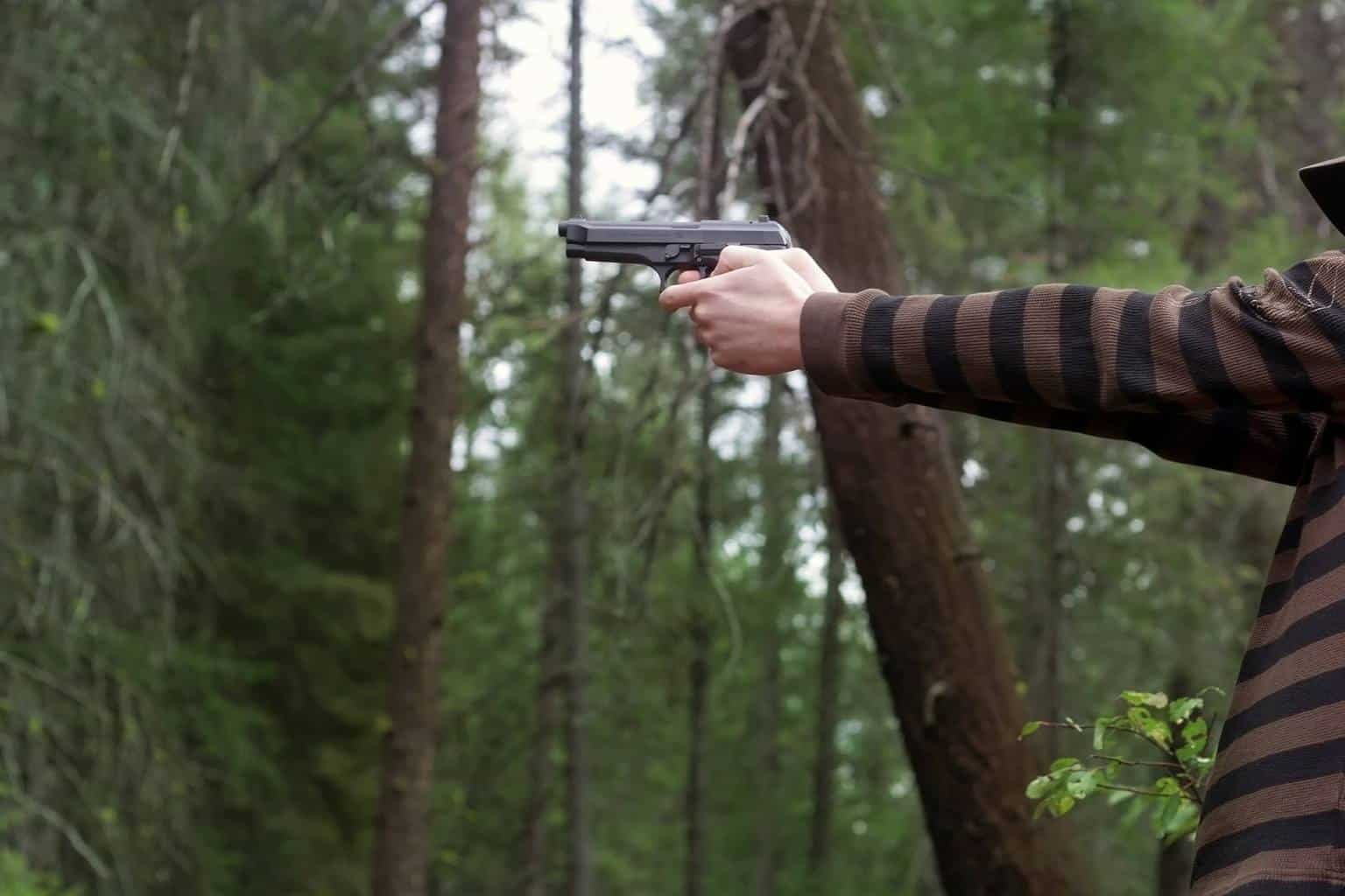 Person holding a gun in a forest