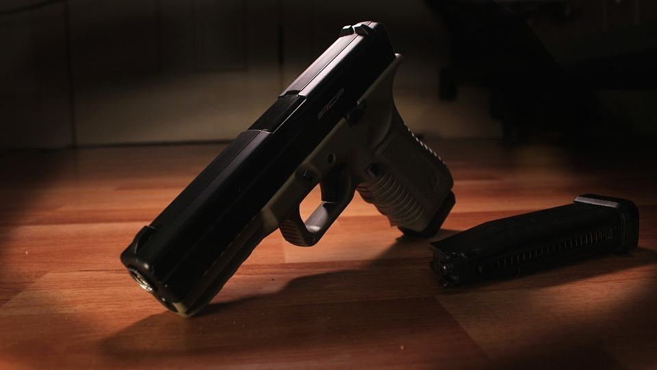Glock handgun and magazine on wooden surface