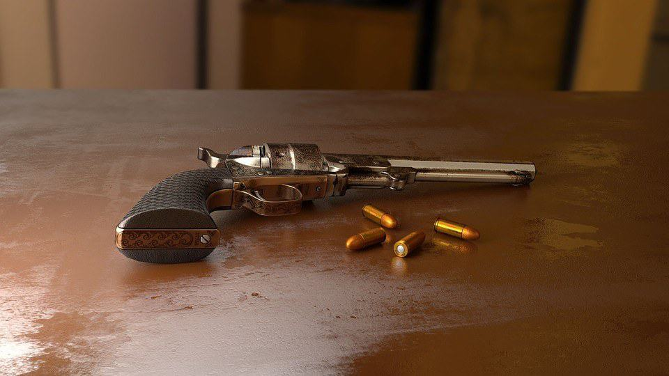 Handgun and bullets on wooden table