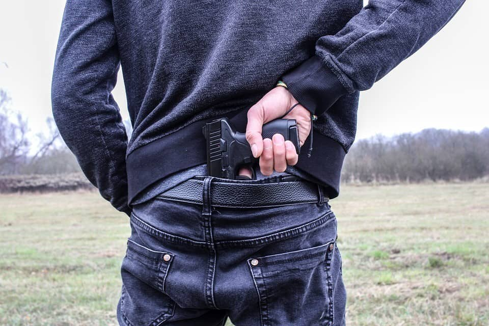 Man concealing gun behind his back