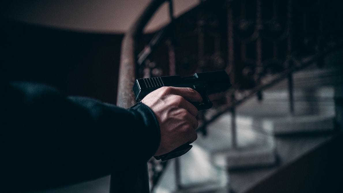 Man pointing a gun near the stairs