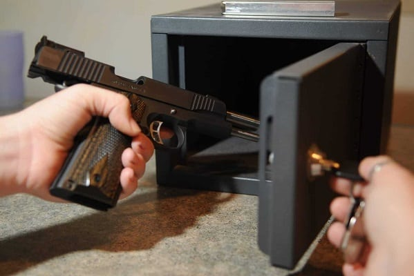 Person storing a gun in a gun safe