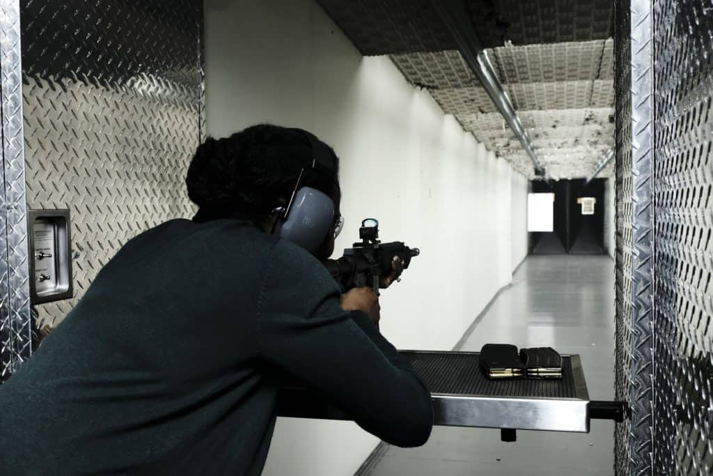 Woman aiming her rifle in a shooting range