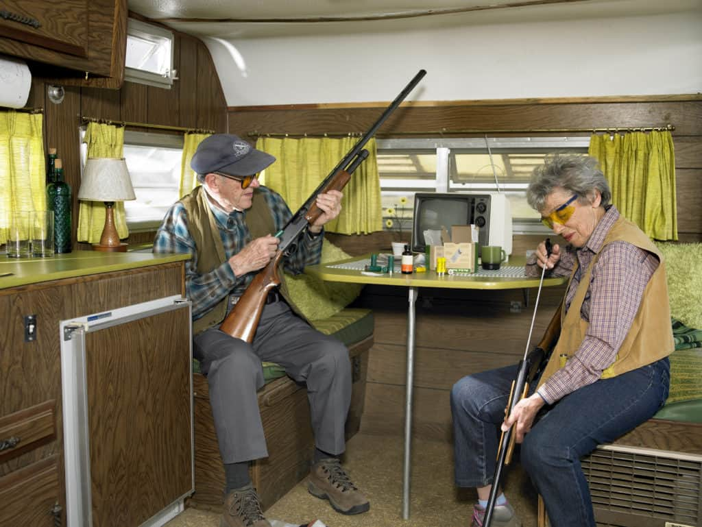 Elderly couple sitting in a trailer both using a cleaning rod for their guns