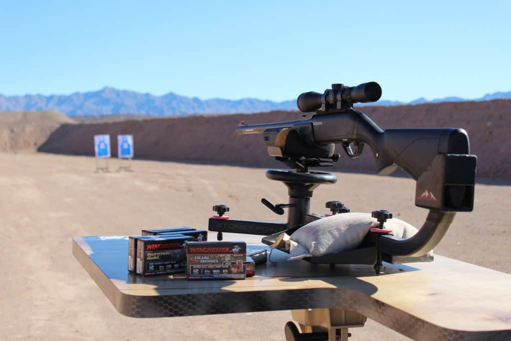 A stationary rifle, boxes of ammunition at an outdoor gun range