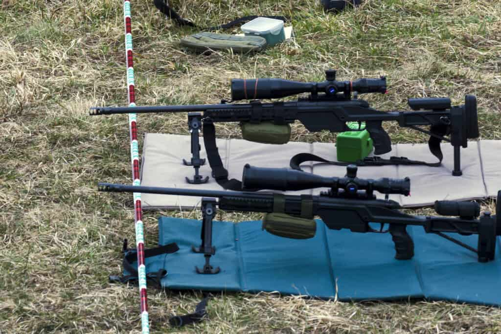 Military rifles aims at a target while being cushioned by a shooting mat on the ground
