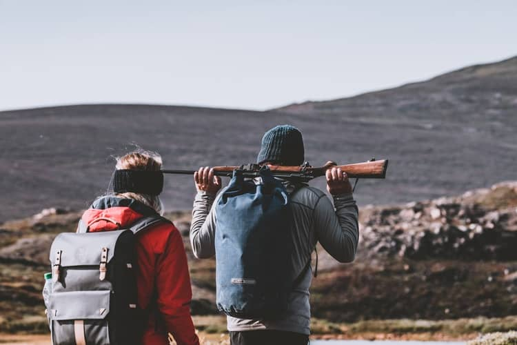 Couple with their backpacks while hunting outdoors