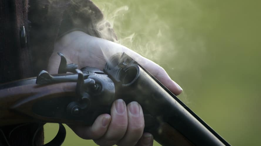 Person holding a freshly fired rifle