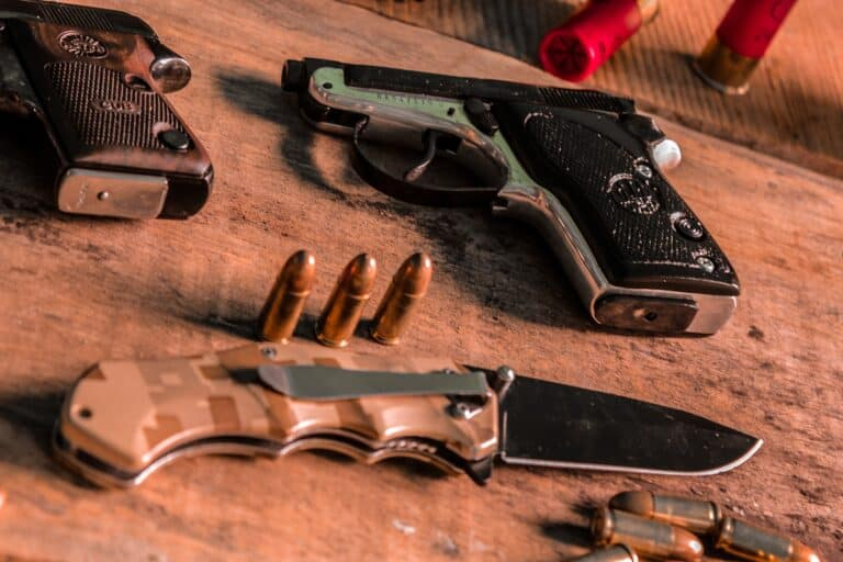 Bullets, knife and handguns in a table
