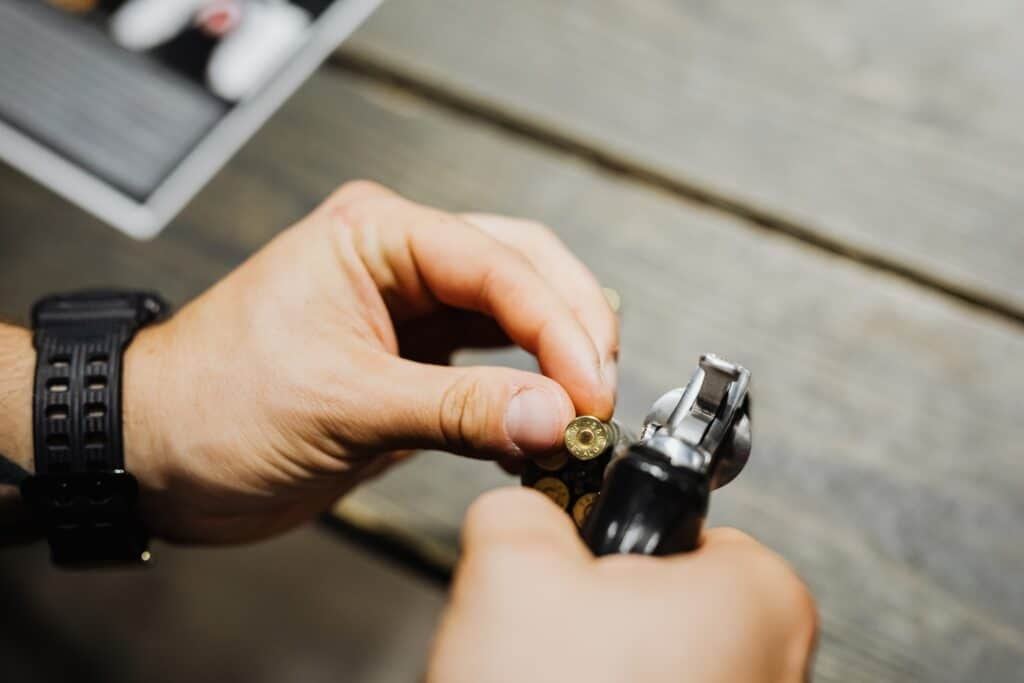 Man loading his pistol with a bullet