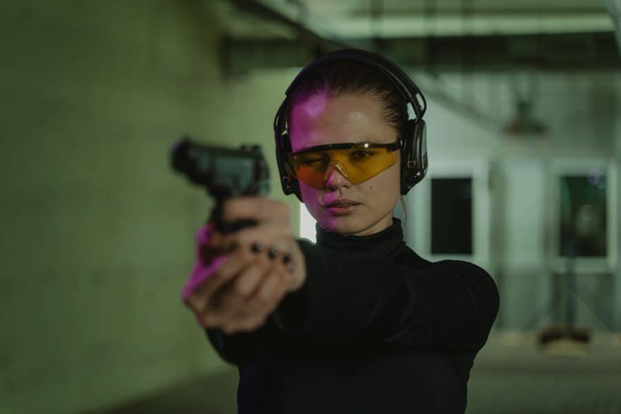 Woman aiming a gun while in a shooting range