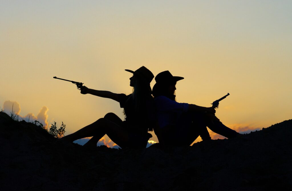 a silhouette of two people holding a gun