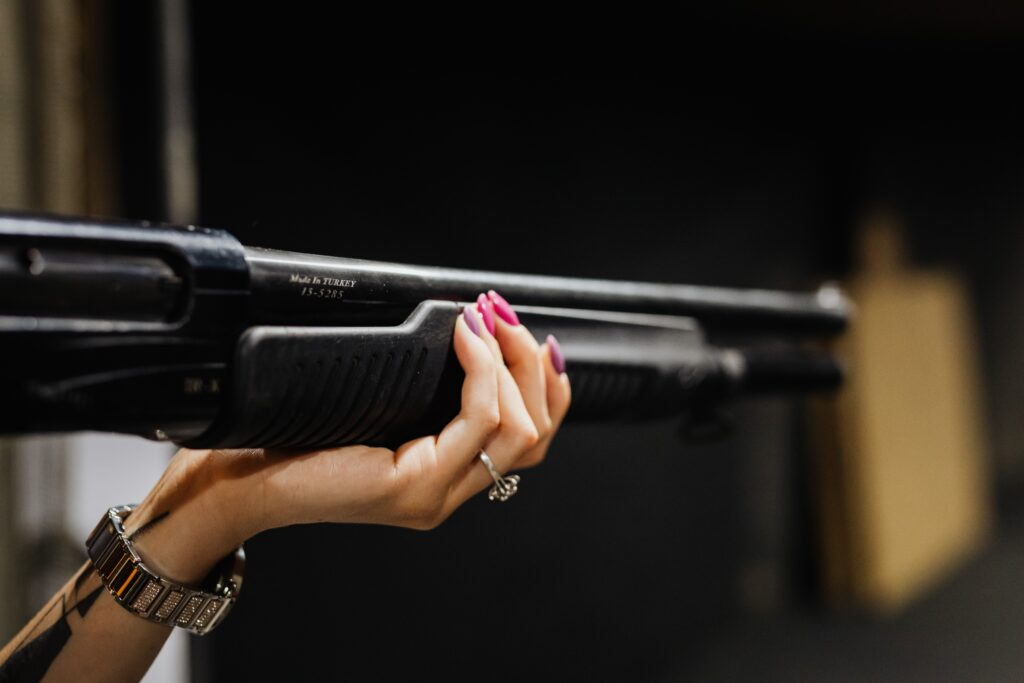 a hand holding a shotgun with painted nails