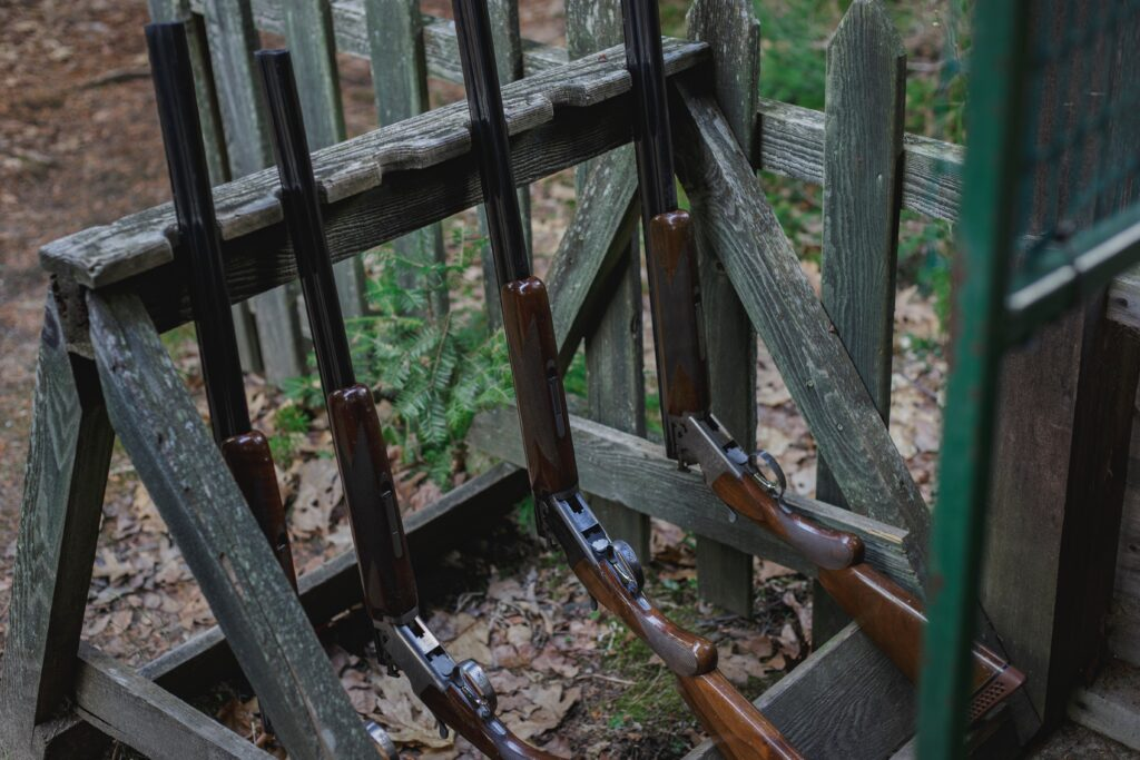 Four shotguns leaning on a wood