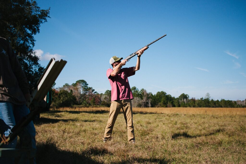 A man aiming a shotgun to the sky in an open field