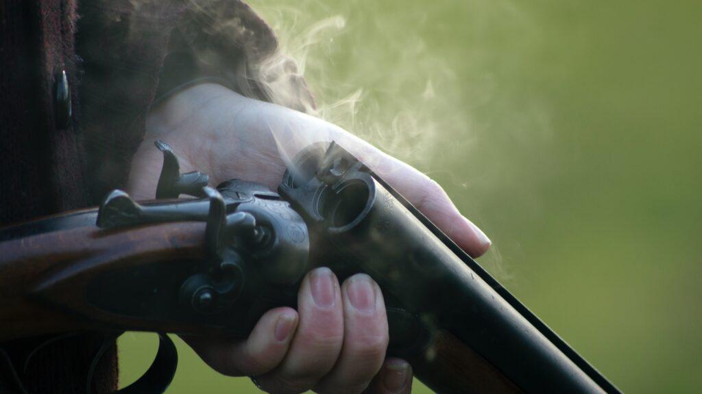 A shotgun producing smoke