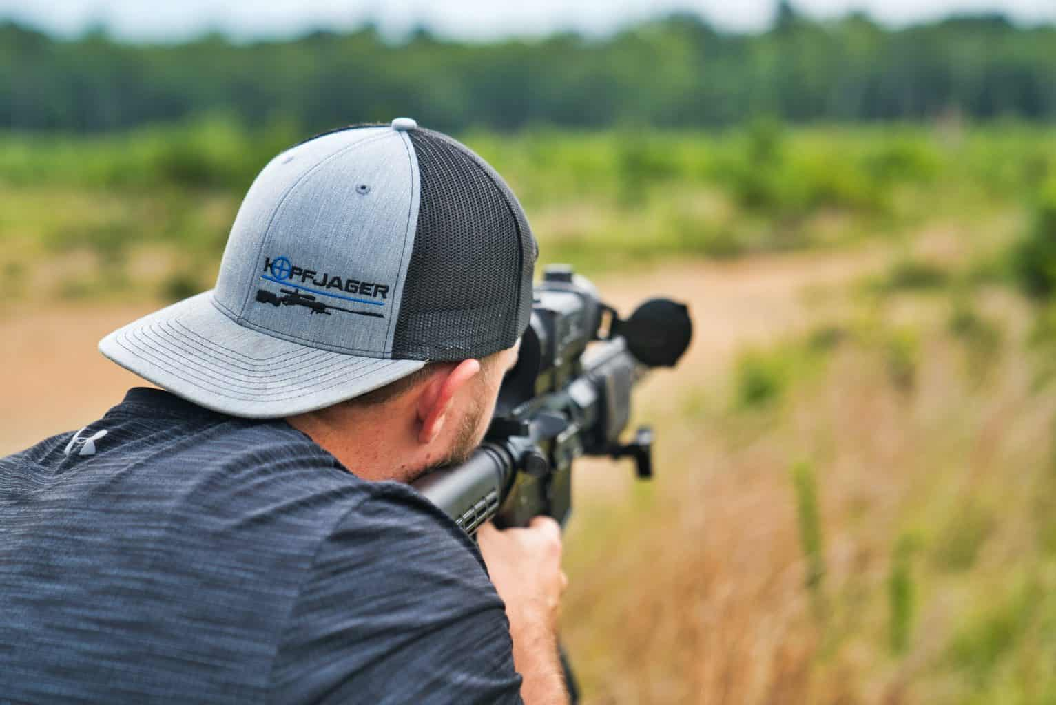 person wearing hat shooting in an open area