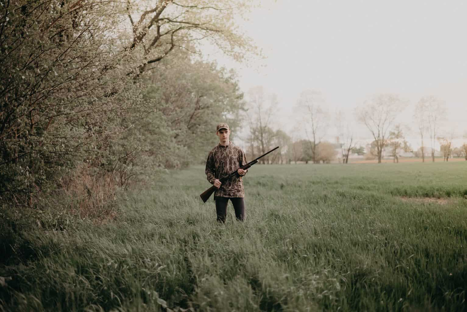 person holding a rifle in an open area with a lot of grass
