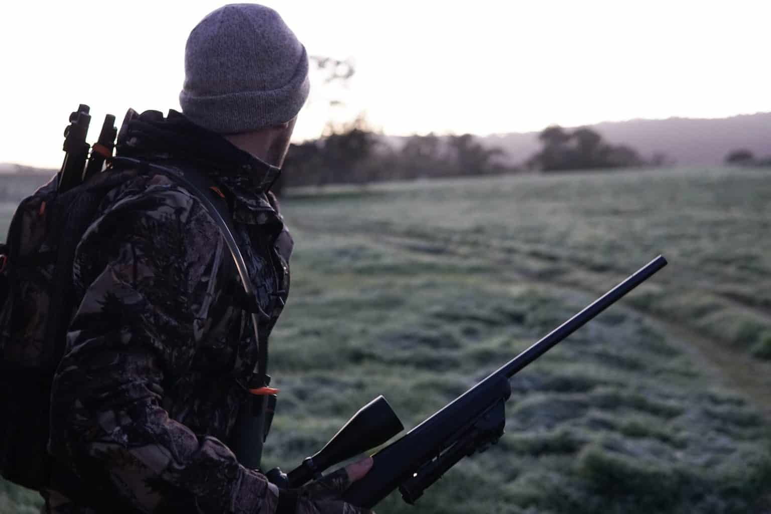 man holding a rifle looking out into the landscape