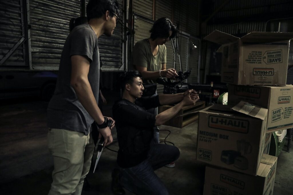 three people in a warehouse holding guns