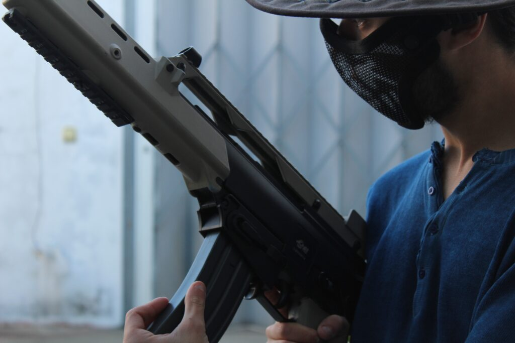 person wearing a mask holding a rifle
