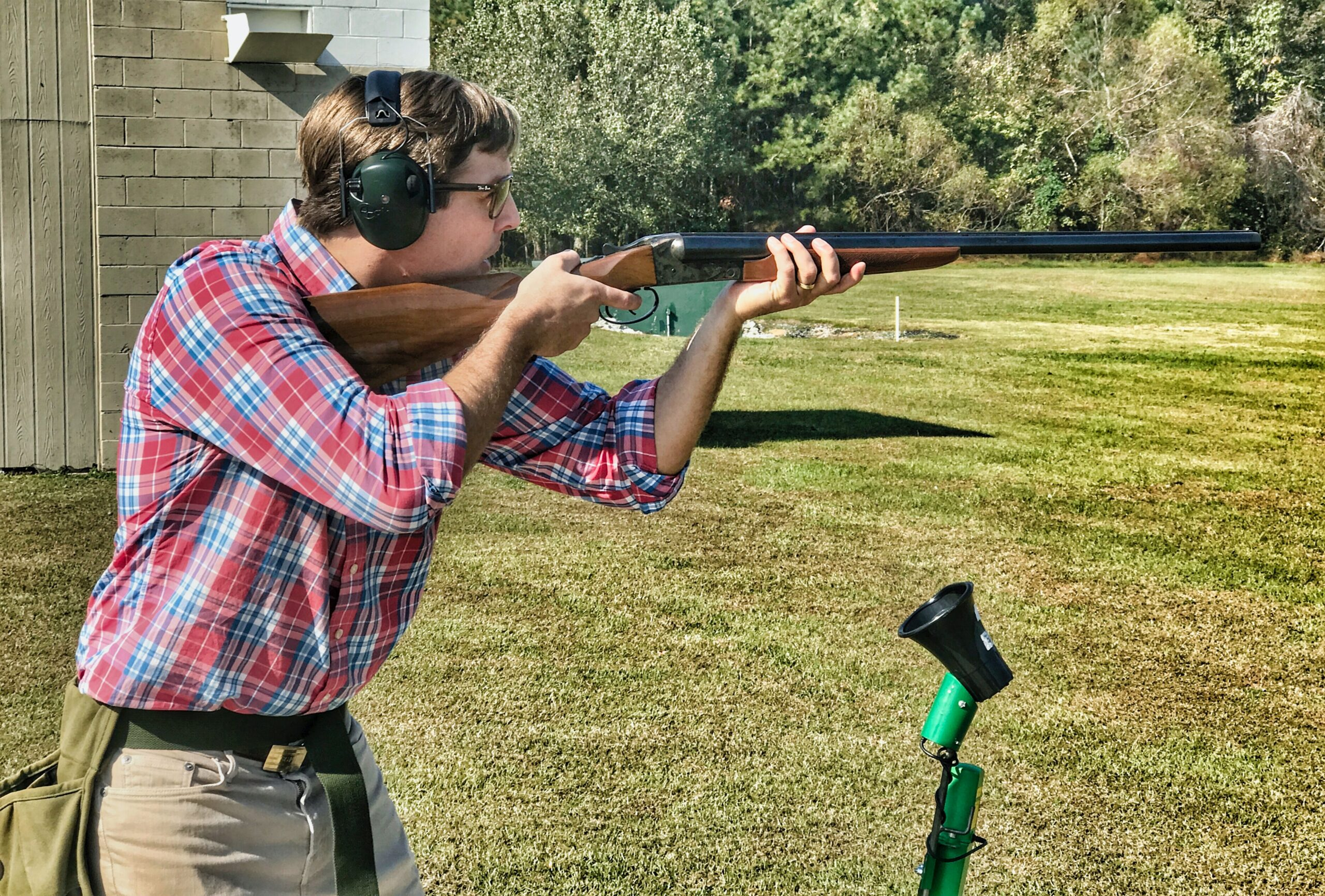 Guy in red and blue plaid polo shooting a rifle