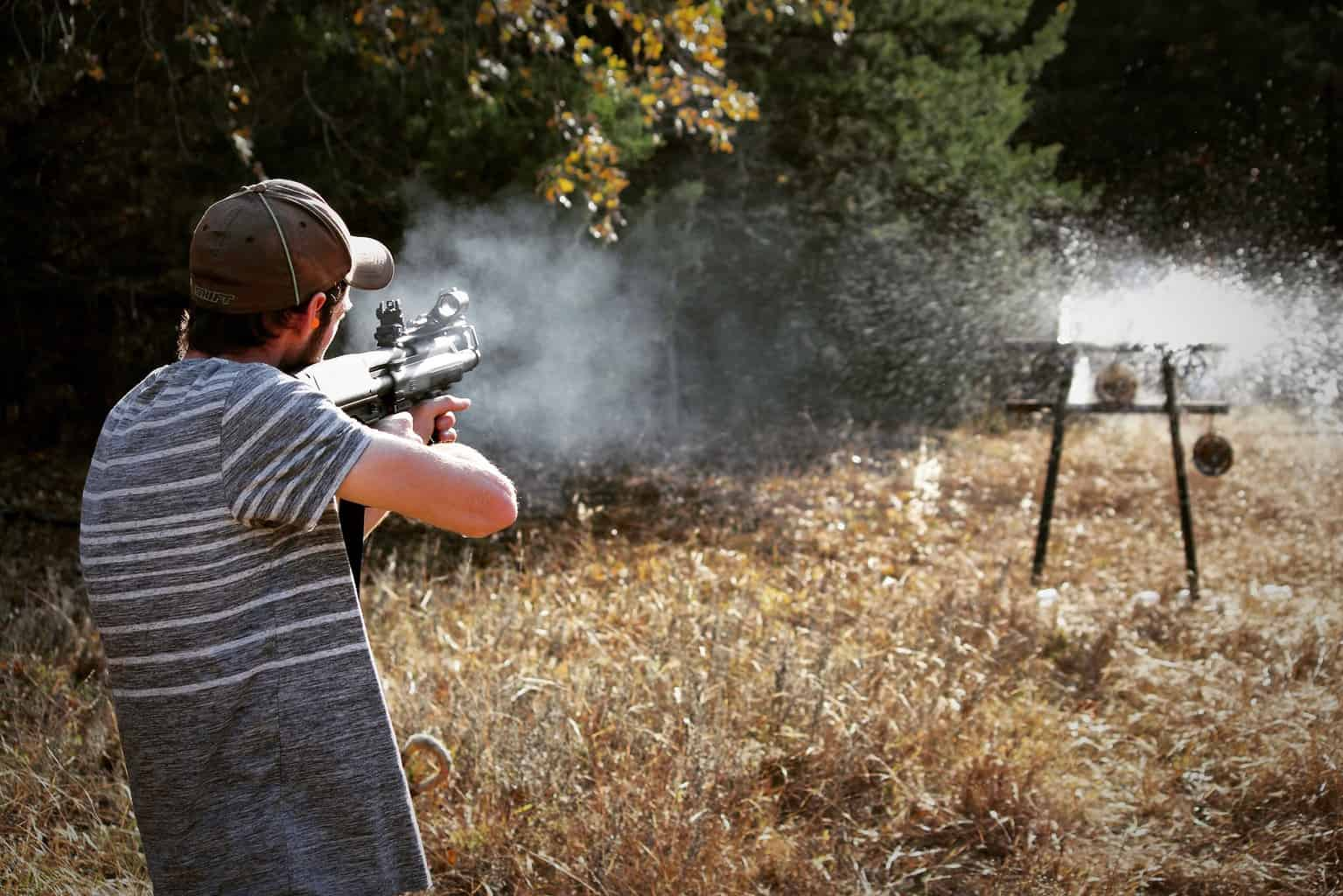 Guy wearing a cap and gray striped shirt shoot a target with a rifle