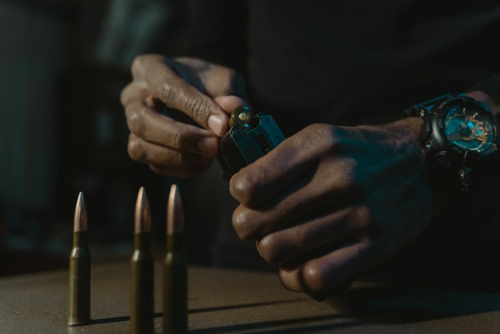 Hand reloading a gun magazine and bullets on a desk