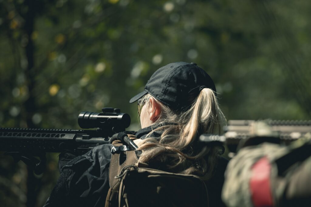 A woman waring a cap and jacket sniping through rifle scope