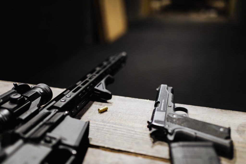 Semi automatic pistol and a rifle on wooden tableen desk