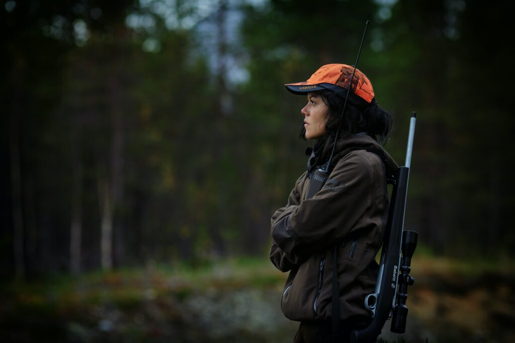 A person wearing an orange cap and carrying a sniper hunting rifle