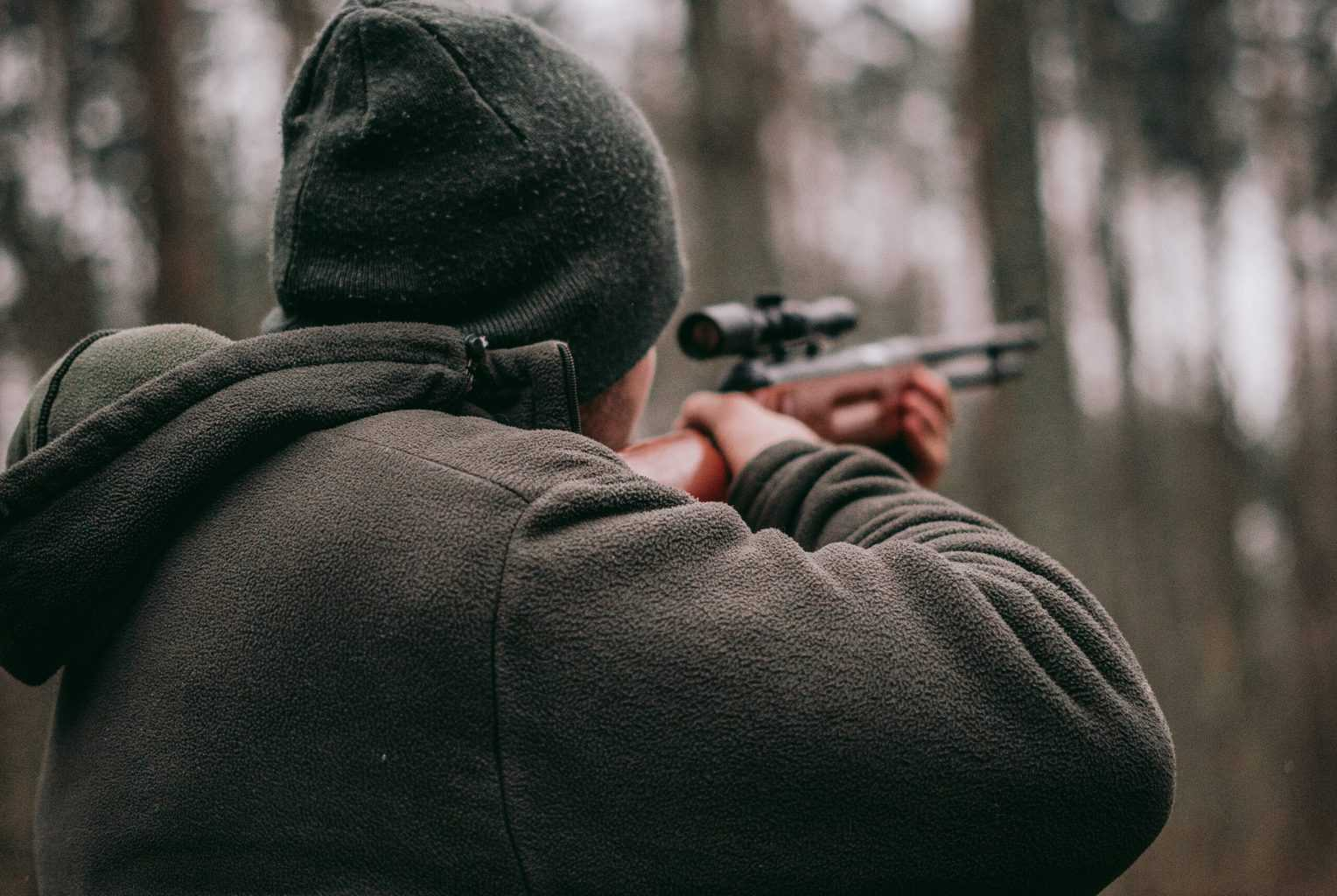 Rear view of a person aiming a sniper hunting rifle