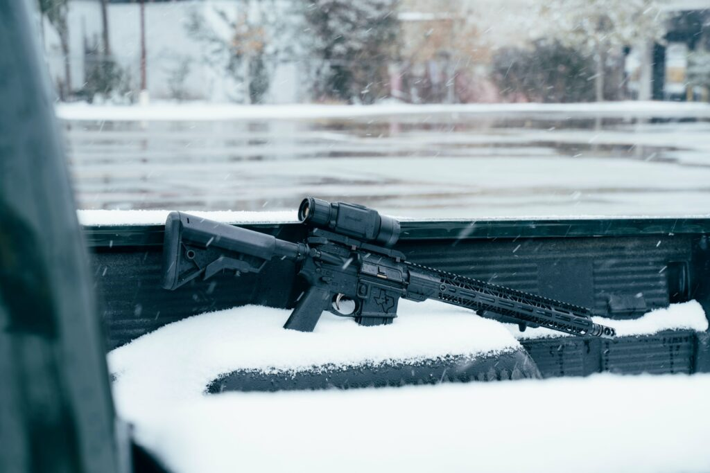 A firearm partially covered with snow in the ground